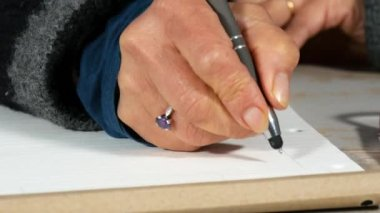 Close up of hand of woman taking notes