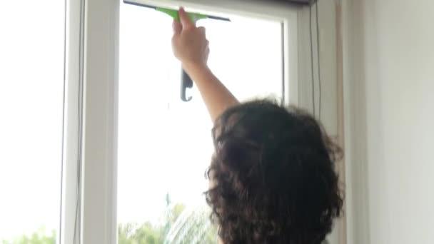 žena mytí oken jejího domu