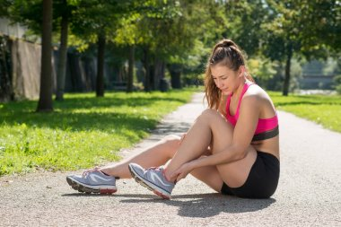 young woman runner touching foot in pain outdoors