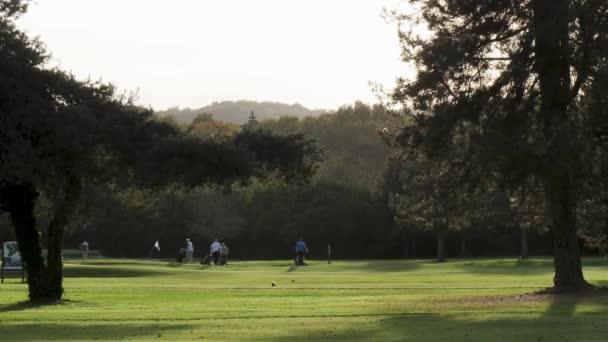 Golfové hřiště při západu slunce s golfisty