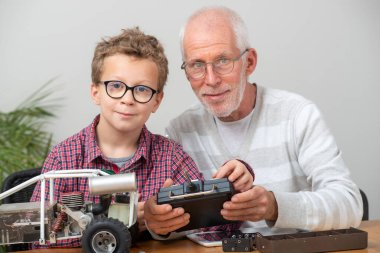 grandpa and son little boy repairing  model radio-controlled car at home