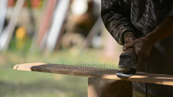 Truhlářem pracuje s elektrická pračka a zpracovává dřevěné výrobky. Tesař s kapesní elektrická pračka v rukou na dřevě.