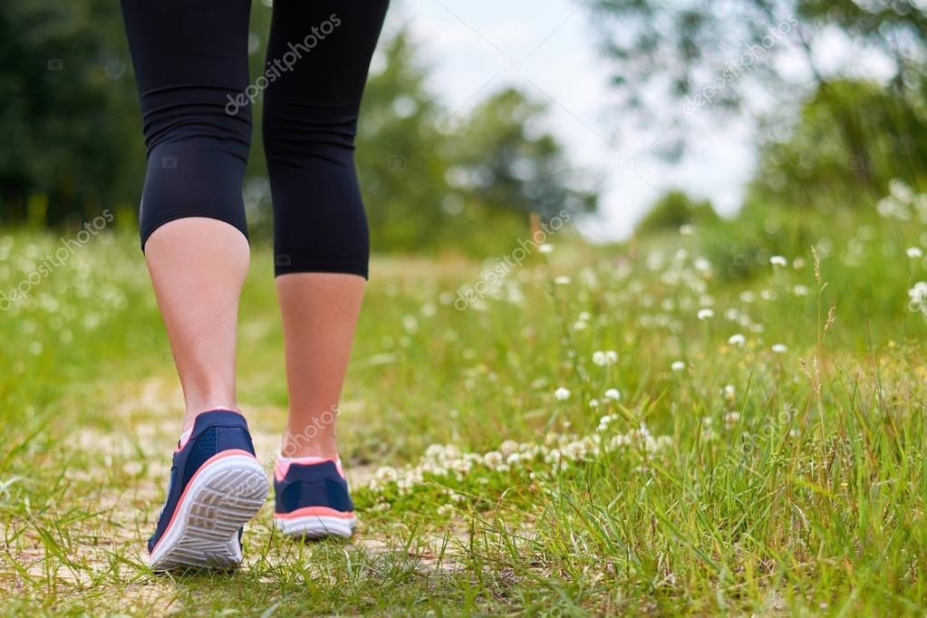 Girl is engaged in cardio runs through forest in sneakers, only legs are visible, legs and sneakers