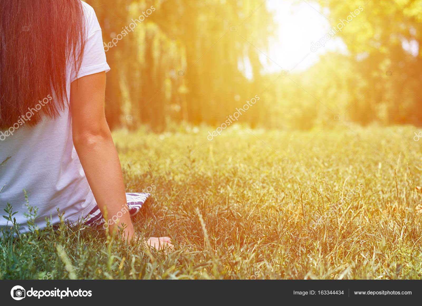Girl sitting on grass and dreaming looking into the distance