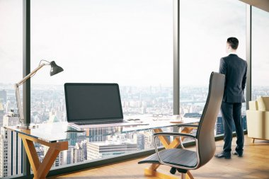 Side view of young man looking out of window in modern office interior with blank laptop and city view. Mock up, 3D Rendering