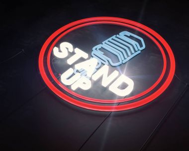 Close up of illuminated retro stand up microphone icon on dark background. Laughter concept.