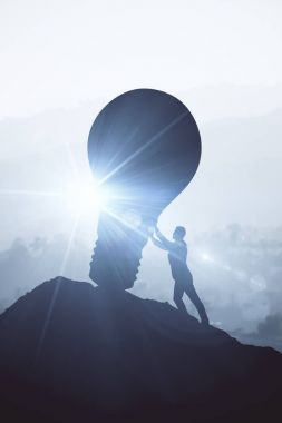 Backlit image of businessman pushing boulder uphill. Bright background with sunlight. Idea concept.
