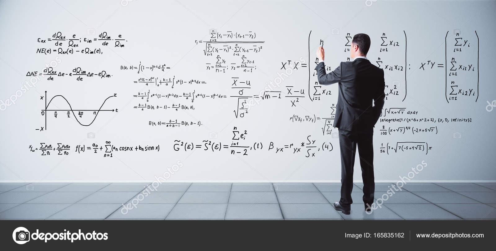 Vista posteriore di giovane uomo daffari scrivere formule ...