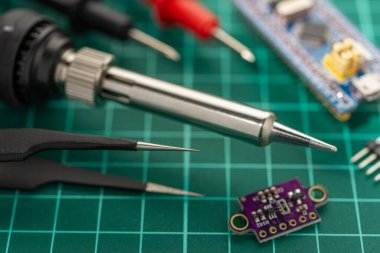 Electronics Development Concept. Hobbies are electronics. Soldering iron and tools on the desktop.