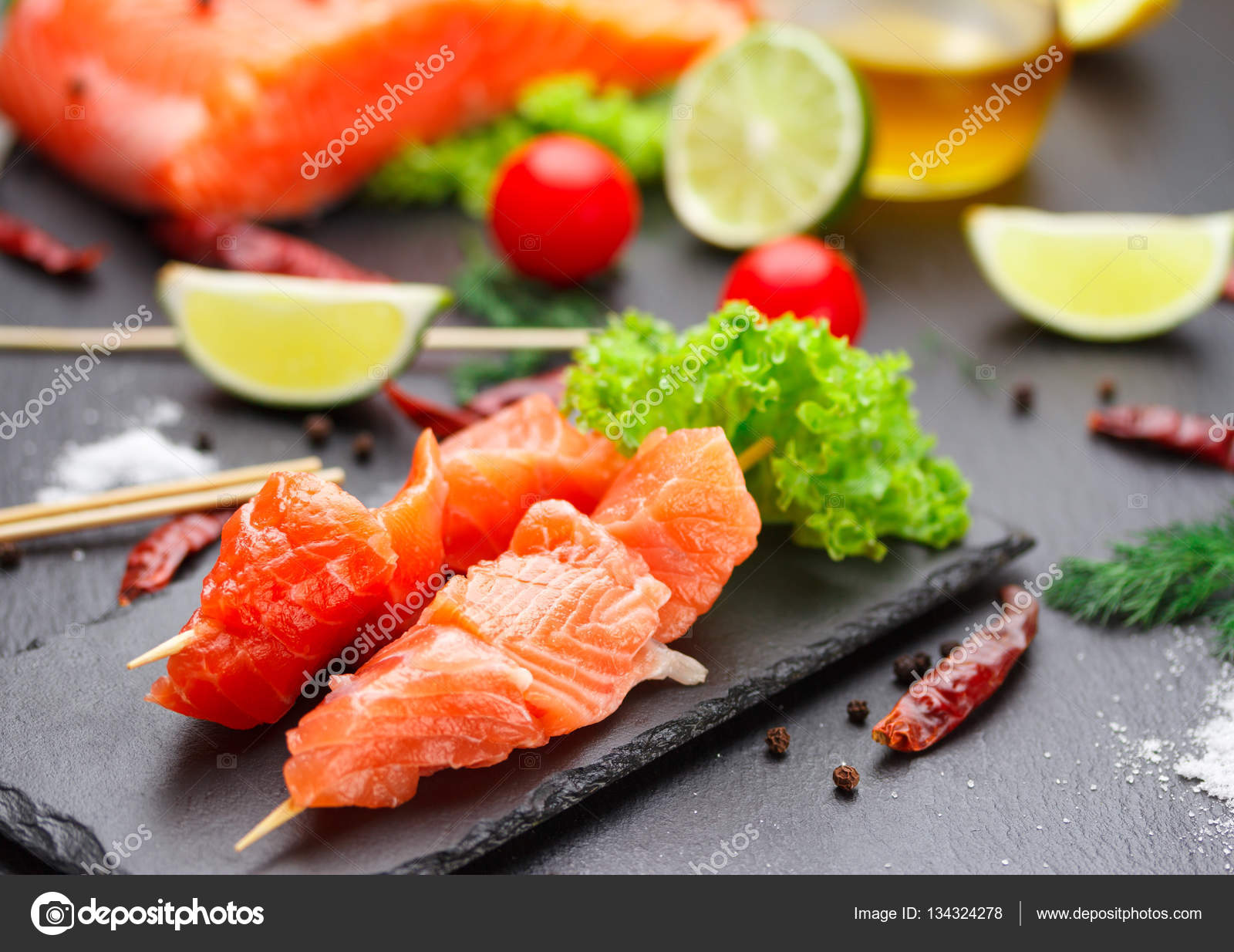 Raw Salmon Skewers On A Stone Plate Tomatoes Lime And Lettuce For