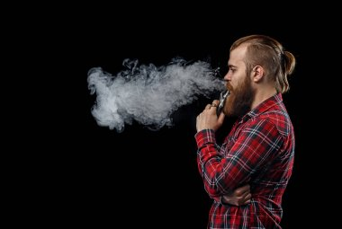 Vaping man holding a mod. A cloud of vapor. Black background. Studio shooting.