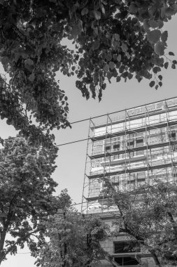Black and white photo of a multi-storey residential building under construction and crane on a background of blue sky