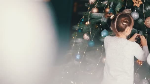 rear view of a little girl decorating a Christmas tree