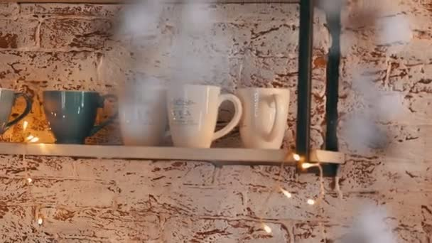 šálky na podkrovních kuchyňských policích zdobené zářícími girlandami