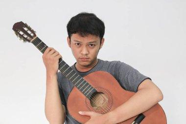 Funny asian man in grey t-shirt posing in studio with guitar