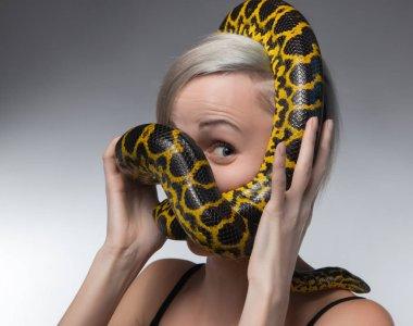 Blond woman and strangling yellow anaconda