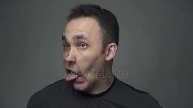 Brunette young man shaking tongue