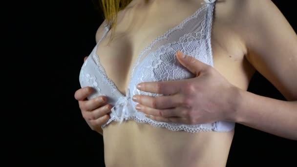 Mladá žena třesoucí prsu