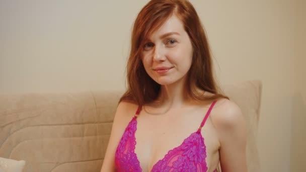 Video rothaarige Frau im lila Spitzenpyjama im Innenraum ihres Hauses
