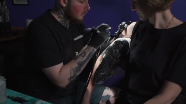 Shooting of man doing black tattoo of snake for woman