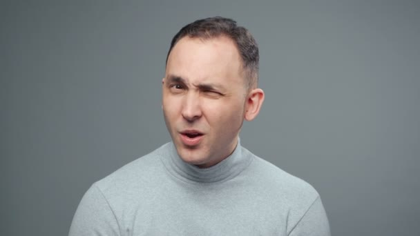 Video of young sceptical man in turtleneck