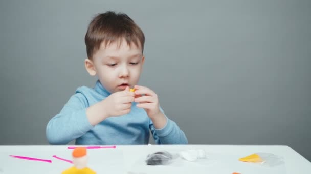 Footage of four year old boy sculpting in plasticine on gray background