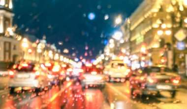 Defocused abstract rush hour with rain drops at night - Bokeh of moving cars stuck in traffic jam on Nevsky Prospekt in Saint Petersburg at blue hour - Blurred postcard on warm vivid filtered look