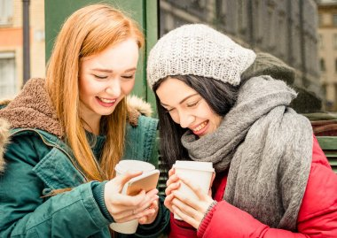 Happy girlfriends best friend having fun with coffee takeaway cup in autumn season - Friendship concept with joyful girls sharing time together with smartphone and winter clothes - Bright vivid filter