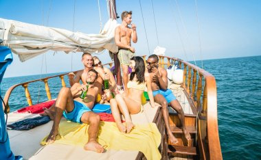 Happy multiracial friends drinking beer and having fun at sail boat party tour - Friendship concept with young multi racial people toasting together on sailboat - Travel lifestyle exclusive location