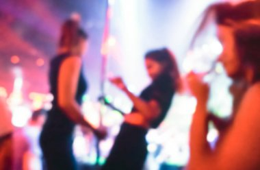 Abstract blurred drunk women moving on pole and dancing at music night festival event - Defocused image of disco club party with color spotlight - Nightlife entertainment concept - Vivid purple filter