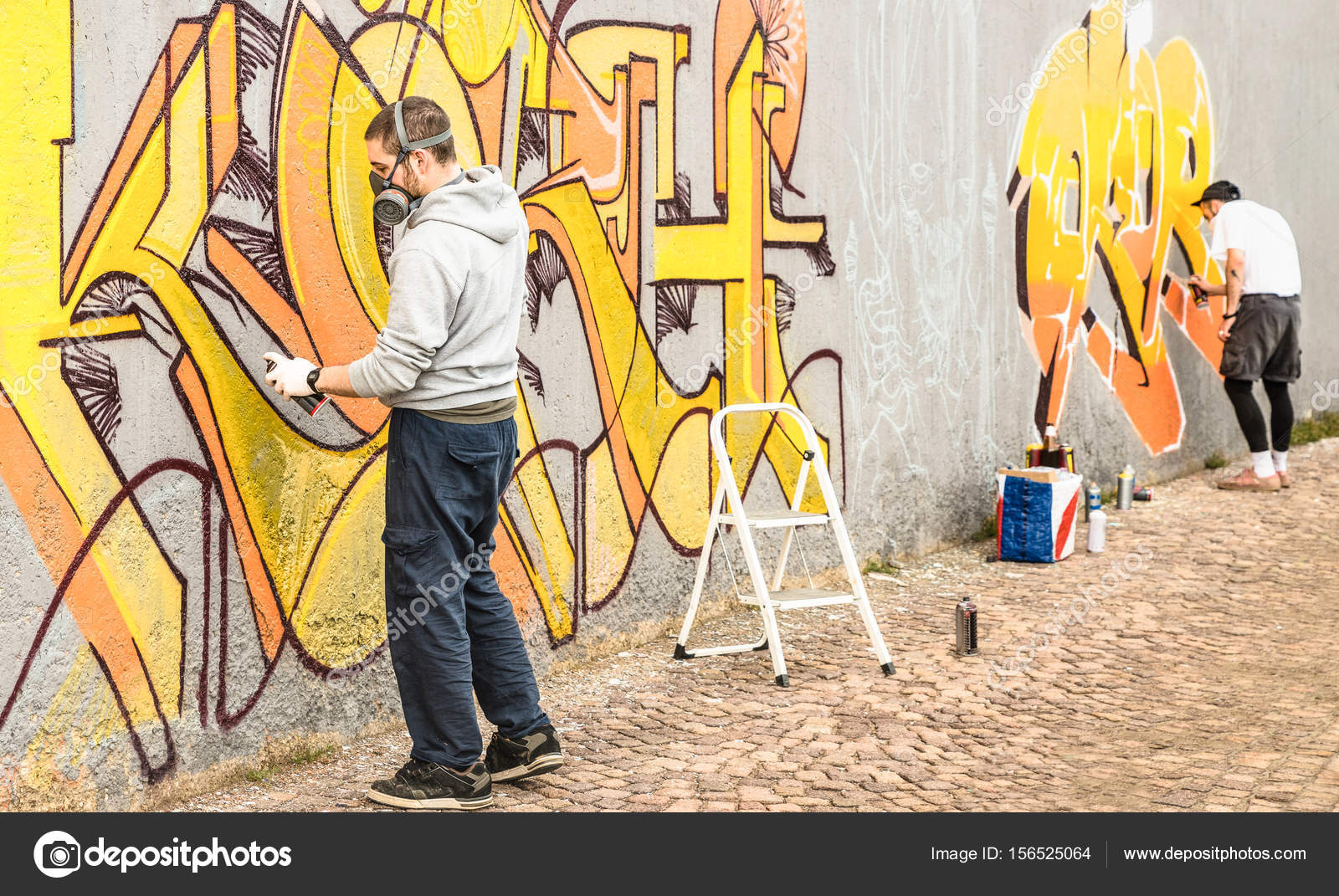 Urban street artists painting colorful graffiti on generic wall ...