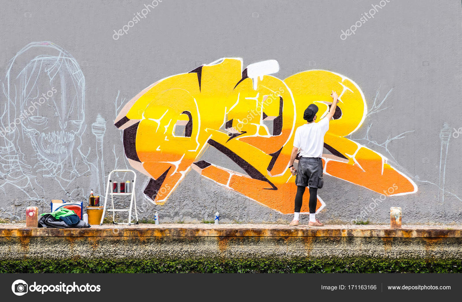 Street artist painting colored graffiti on public space wall ...