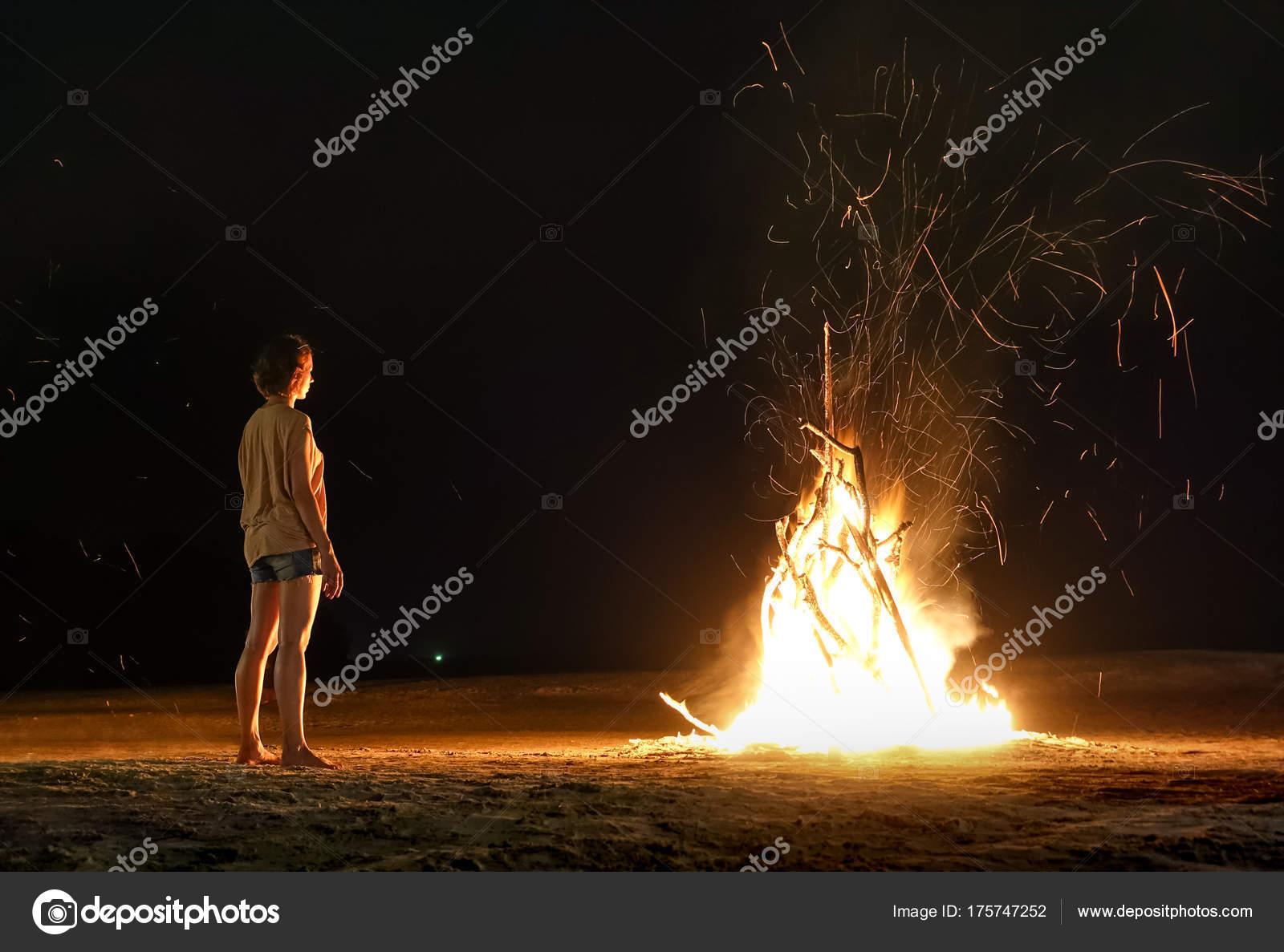 Jonge vrouw reiziger gevoel hitte van strand vreugdevuur met vonken ...