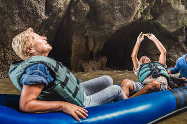 Happy retired senior couple having fun at travel around world - Active elderly concept with people on kayak cave excursion at Phang Nga bay Thailand - Mature people trip lifestyle - Dark natural light