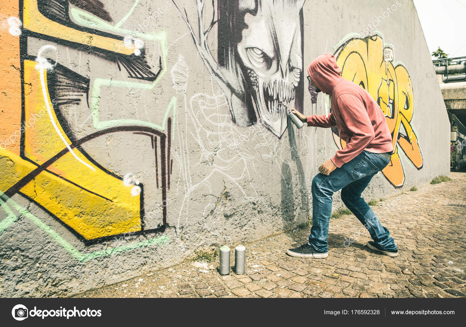 Street artist painting colorful graffiti on generic wall modern art concept with urban guy performing and preparing live murales with multi color aerosol