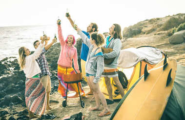 Hipster friends having fun together at beach camping party - Friendship travel concept with young people travelers toasting and drinking bottled beer at summer surf camp - Bright vintage filter