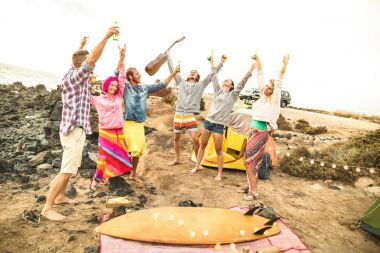 Hippie friends having fun together at beach camping music party - Friendship travel concept with young people wanderers dancing and drinking beer at summer surf camp - Warm bright vintage filter