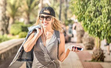 Young woman fashion travel blogger listening music podcast at city trip - Wanderlust vacation concept with adventure girl tourist wanderer on world tour excursion in Tenerife - Warm bright filter
