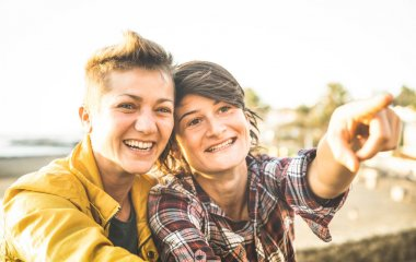 Happy girlfriends in love sharing time together at travel trip pointing on horizon - Women friendship concept with girls couple having fun on fashion clothes outdoors - Bright warm sunset filter