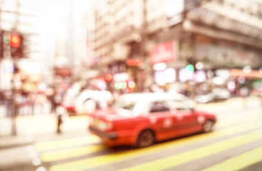 Blurred defocused abstract background of red taxi cab on zebra crossing with soft pink pastel filter - Crowded Nathan Road street in Hong Kong city center during rush hour in urban business area