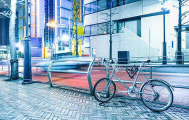 Night scene with parked bicycle and blurred speeding car in the city center of Tokyo capital of Japan - Urban travel concept with modern bike on bright azure color filter