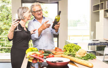 Senior couple cooking healthy food and drinking red wine at house kitchen - Retired people at home preparing lunch with fresh vegetables and bio products - Happy elderly concept with mature pensioner