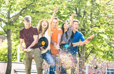 Group of happy excited friends having fun outdoor cheering with confetti - Young people enjoying spring summer time together at garden party - Youth friendship concept on warm afternoon color filter