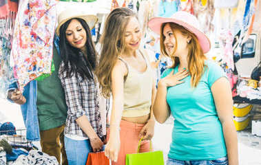 Young pretty women girlfriends at cloth flea market looking for fashion wardrobe - Friendship concept with female best friends having fun and shopping in old town - Bright vintage color tones filter