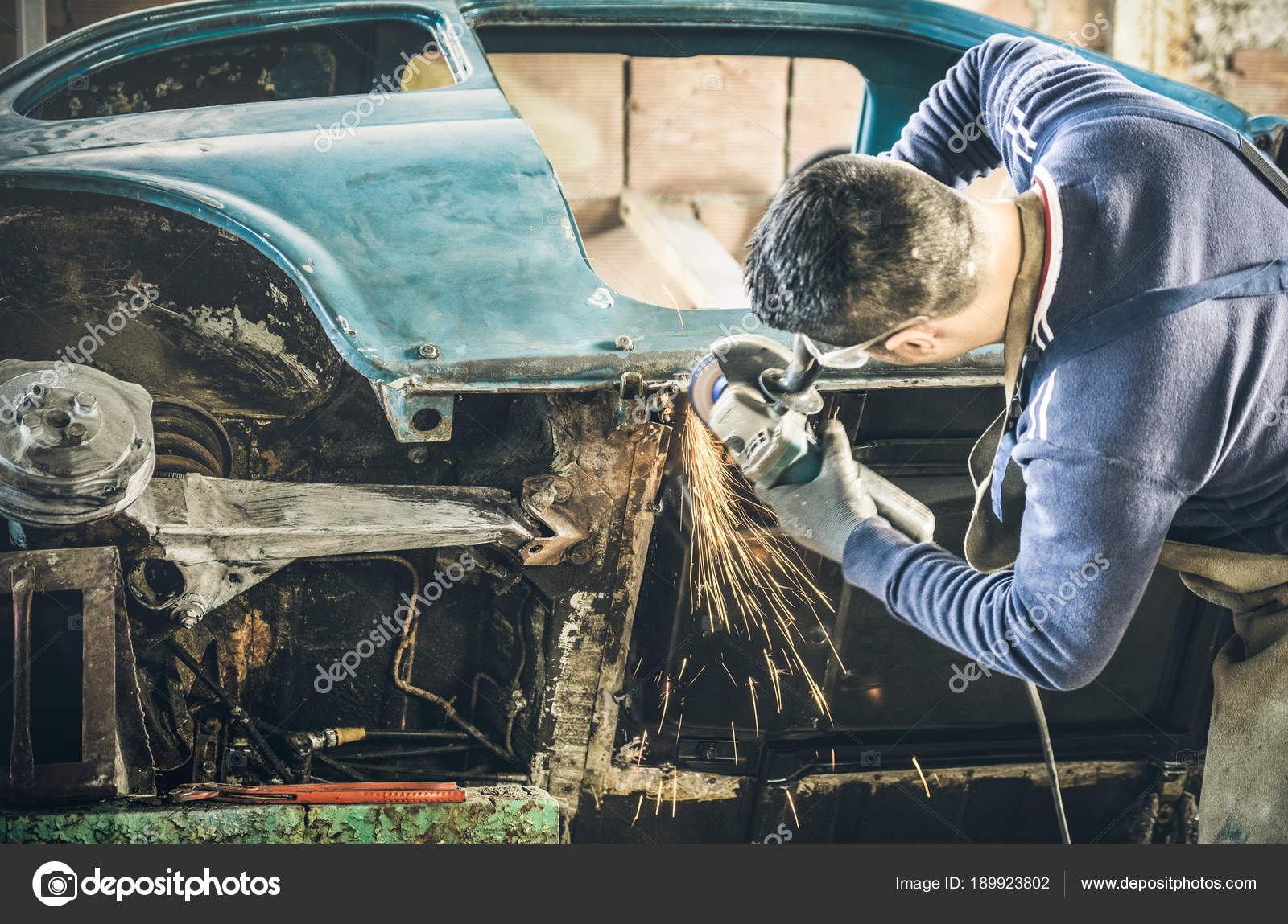 Young man mechanical worker repairing old vintage car body with ...