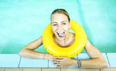 Happy woman in clear water looking at camera with bigmouth expression - Young girl at swimming pool class with life buoy - Medical concept of hydrotherapy spa treatment and swim school - Azure filter