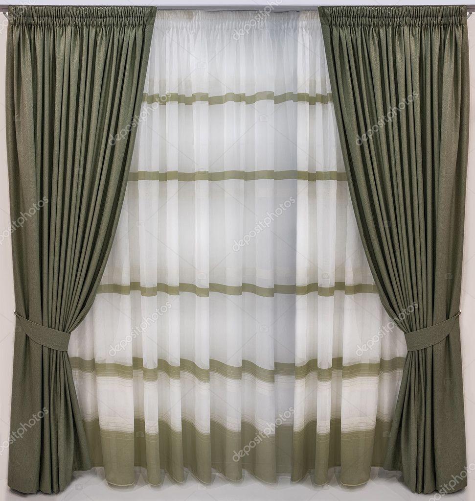 dikke gordijnen van stof wol en doorschijnende tule met de strips hebben hangen op op een kroonlijst van twee rijen op de speciale tape foto van fotiy