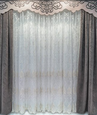 The straight, brown curtains of the dense natural material, a light tulle organza, hard pelmet with a pattern