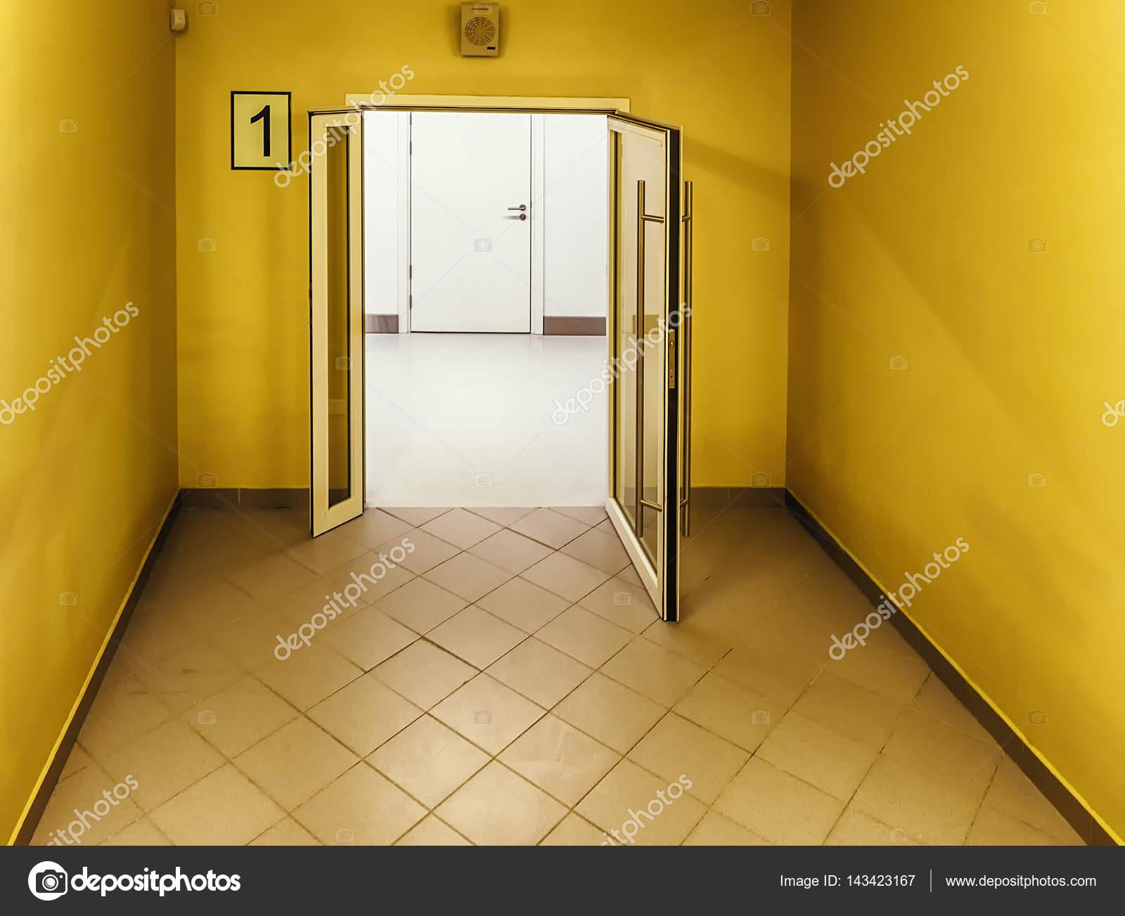 Heldere gele kleur trap met de deur open naar een office corridor