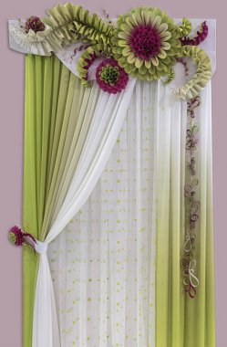 Delicate green - yellow curtains of light fabric, a tulle and luxurious flowers made from starched material.